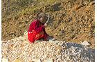 Lkw-Fahren in Nepal, Straßenbau, Steineklopfen, Handarbeit